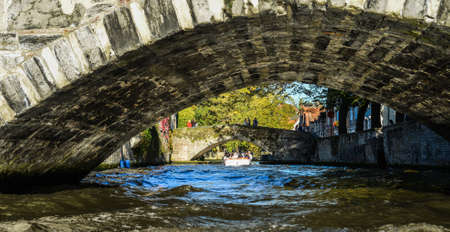 Bruges, Belgium - Oct 5, 2018. Stone ancient bridge with the canal in sunny day. Bruges is a medieval fairy-tale town and Belgium most visited city with 7.8 million people every year.