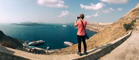 Santorini, Greece - Oct 10, 2018. An Asian man enjoying the beautiful seascape on Santorini island, Greece. Summer landscape, turquoise sea and blue sky. 新聞圖片