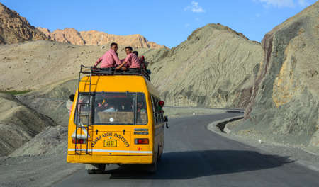 Ladakh, India - Jul 16, 2015. School bus on a rural road in Ladakh, India. Ladakh is the highest plateau in the state of Jammu & Kashmir with much of it being over 3000m.