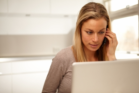 Beautiful woman listening carefully to the conversation on her mobile phone while consulting her laptop screen Stock Photo - 17458022