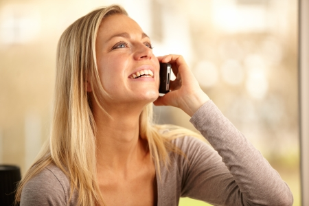 Happy woman socialising with her friends over her mobile phone in a telecommunications concept Stock Photo