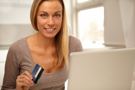 Beautiful woman standing alongsie her laptop screen with her credit card in her hand about to make an online purchase  Stock Photo