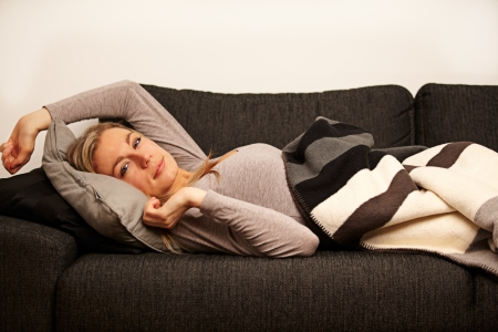 recuperating: Beautiful sleepy woman just waking up and stretching under cover of a blanket on a sofa Stock Photo