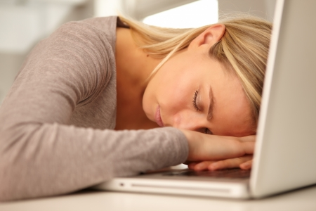 A beautiful young blonde woman sits fast asleep with her head resting on her hands across her laptop keyboard