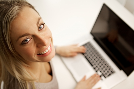 High angle view of a beautiful woman looking up at the camera with a lovely friendly smile working on her laptop in a home or company office