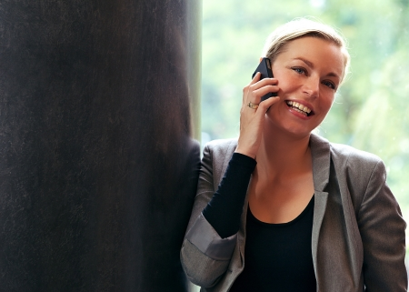 Vivacious beautiful blonde woman with a lovely smile leaning against a pillar using a mobile phone Stock Photo