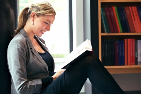 Beautiful woman reading in a library sitting comfortably on the floor with a delightful smile on her face as she enjoys her book
