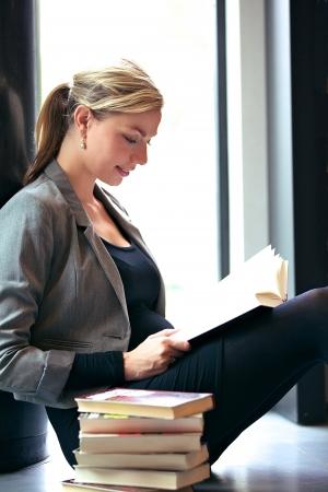 windowsill: Beautiful woman university or post-graduate student studying sitting comfortably on windowsill with a stack of textbooks alongside her