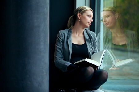 musing: Lonely woman sitting in a windowsill with a book reading and dreaming as she gazes out through the window with a serious expression with copysapce