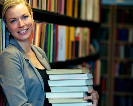Enthousiaste bibliothécaire ou un étudiant debout à l'intérieur d'une bibliothèque portant une pile de gros livres, soit pour l'enseignement et la recherche ou de l'inventaire qui doit être remplacé sur les étagères