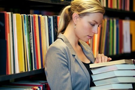 absorbed: Serious attractive woman with a stack of books in her arms standing reading in a library with bookshelves full of books Stock Photo