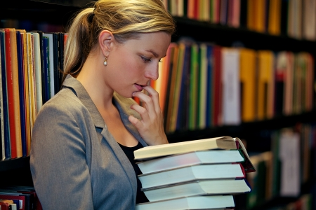Beautiful female student standing in a library deeply immersed in a book wth her finger to her lip in thought photo