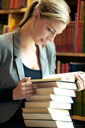 Beautiful blonde woman with a pile of books doing research in a library and standing reading from the top of the pile Stock Photo