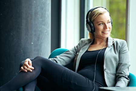 Beautiful blonde woman with a lovely smile relaxing in an armchair listening to music on a pair of stereo headphones Stock Photo