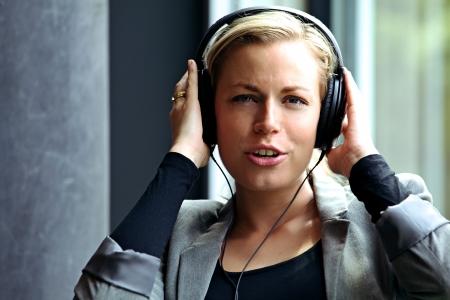 Happy vivacious woman enjoying herself singing along to music on her headphones Stock Photo