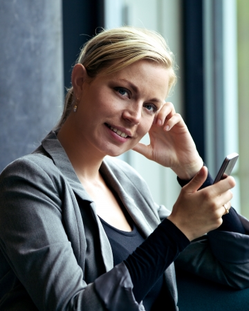 Smiling attractive woman holding up her mobile phone while texting and receiving messages