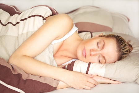 Beautiful blonde woman sleeping peacefully in her bed under her brown patterned duvet with a calm serene expression Stock Photo - 17458085