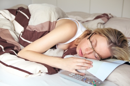 exhaustion: Woman suffering from exhaustion fallen asleep in her reading glasses on the document she was reading