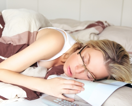 Exhausted woman sleeping in her glasses collapsed on top of the document she was reading Stock Photo - 17458054