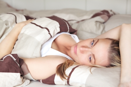 Beautiful young blonde woman lying back on her bed daydreaming as she relaxes having a lazy day Stock Photo - 17458093