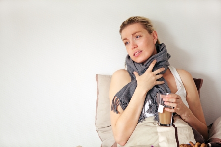 Beautiful pregnant woman with a pained expression sitting up against a pillow clutching a scarf around her neck suffering with seasonal flu Stock Photo - 17458088