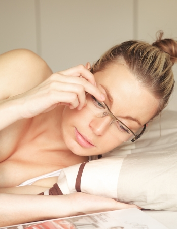Beautiful young blonde woman confined to bed lying reading with her head raised above the pillow and her hand supporting her glasses Stock Photo - 17458074