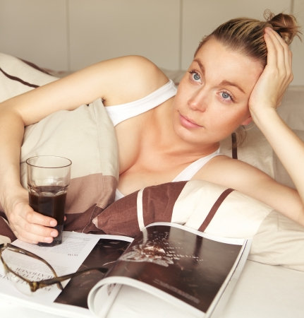 Attractive young bored woman sick in bed with a magazine and drink staring upwards lost in thought daydreaming Stock Photo - 17458066