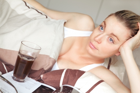 Bored woman confined to bed during her pregnancy or recovering from an illnes relaxing in her bed with a magazine and glass of refreshment alongside her Stock Photo - 17458089