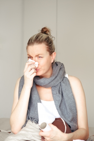 Young woman ill with seasonal chills and flu sitting in bed blowing her nose on a tissue with a scarf around her neck Stock Photo - 17458091