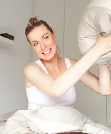Beautiful playful woman sitting in her bed poised to throw a pillow during a mock fight with a look of glee on her face Stock Photo - 17458058