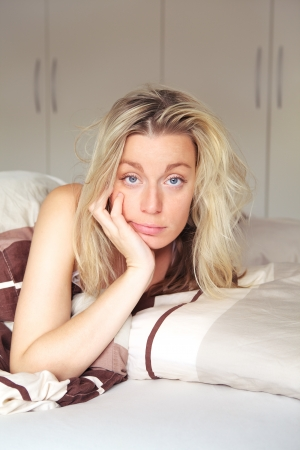 unmotivated: Bored woman confined to her bed while recouperating from an illness looking at the camera with a depondent expression