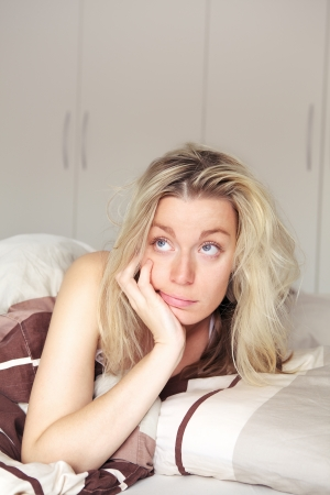 Bored young woman relaxing in her bed recouperating from a illness lying on her stomach looking upwards daydreaming Stock Photo - 17458096