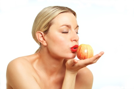 puckering lips: A female model wearing bright red lipstick kissing an Apple. Stock Photo