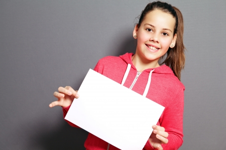 Beautiful little girl with a lovely smile holding up a blank sheet of paper at a tilted angle in her hands Stock Photo - 17495020