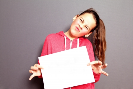 Scornful attractive little girl turning up her nose in dislike holding up a blank sheet of white paper for your text Stock Photo - 17495015