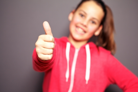 acceptance: Happy young female teenager gives a thumbs up to the camera. Intentional shallow depth of field focusing on the thumb