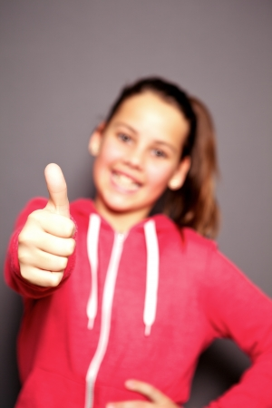 Happy smiling little girl giving a thumbs up of approval to show she is happy and all is well with focus to her thumb, vertical studio portrait on grey Stock Photo - 17495016