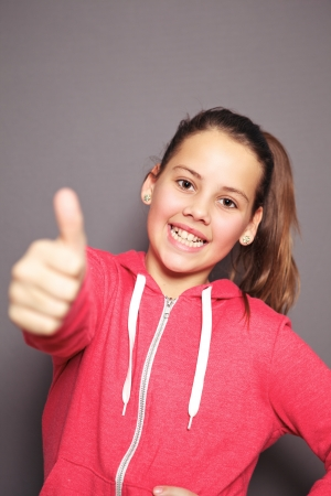 Cheerful young girl with a lovely smile giving a thumbs up of approval to show she is happy, studio half body portrait with focus to her face