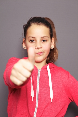 Dubious young girl giving a thumbs up of approval without much enthusiasm as she gives a wry expression showing she is not really sure Stock Photo - 17495026