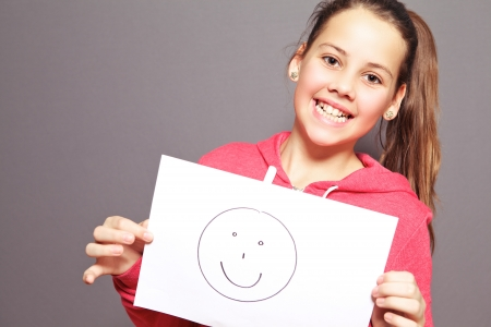 preteen: Happy attractive young girl with a lovely toothy smile holding a smiley drawn on a sheet of white paper, half body studio portrait on grey