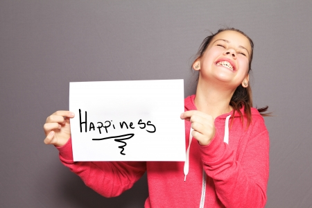 preteen girl: Fun Happiness concept with a young girl holding up a handwritten sign saying Happiness and tilting her head back with a cheeky ear to ear grin