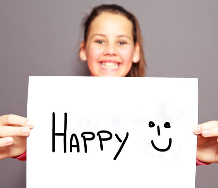 Joyful young girl with a HAPPY sign and smiley face handdrawn on a sheet of white paper with focus to the message photo