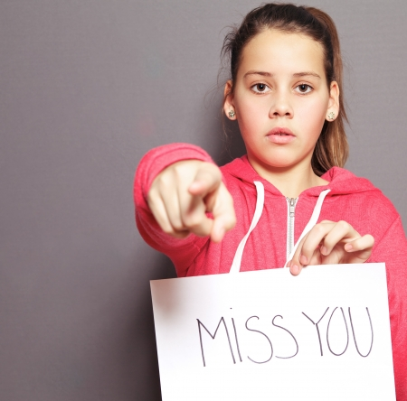 Cute young girl with a doleful expression holding up a sheet of paper with a handwritten MISS YOU and pointing her finger towards the camera, studio portrait on grey photo