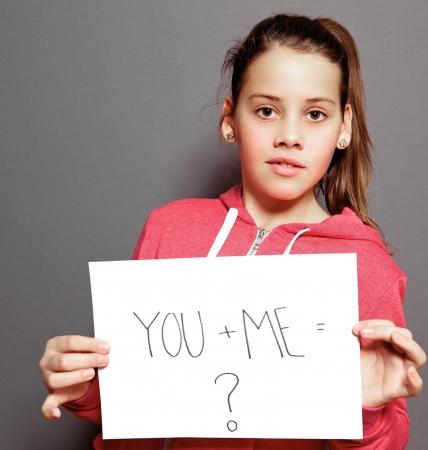 ni�os sosteniendo un cartel: Burlona chica que sostiene una hoja de papel blanco con el mensaje escrito a mano USTED y YO igual signo de interrogaci�n mirando a la c�mara como esperando una respuesta, potrait estudio sobre gris