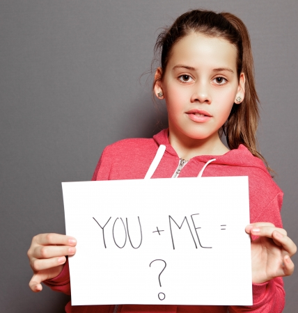 Quizzical little girl holding up a sheet of white paper with the handwritten message YOU and ME equals question mark looking at the camera as though awaiting an answer, studio potrait on grey Stock Photo - 17495007