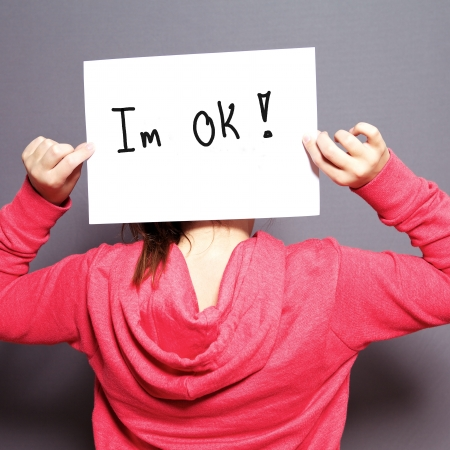 Young child in a pink top standing with her back to the camera holding up a white sheet of paper with the handwritten text Im OK for I am OK Stock Photo - 17495017