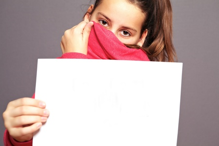 Bashful little girl hiding her face with the collar of her jacket so that just her eyes are visible holding up a blank sheet of white paper photo