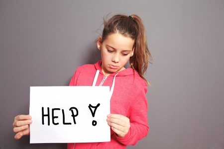 Conceptual image of a sad dejected little girl with a pouting lip standing holding a handwritten HELP sign with an exclamation mark, studio upper body portrait on a grey background with copyspace photo