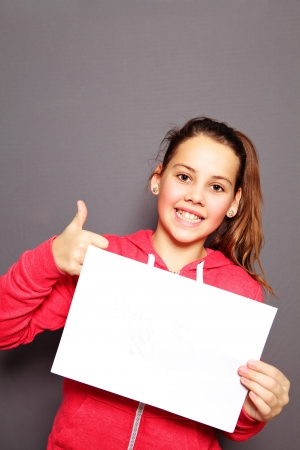 Beautiful smiling happy little girl with blank white sign giving a thumbs up of approval and agreement, studio upper body portrait on a grey background with copyspace photo