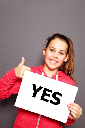 Beautiful enthusiastic happy little girl with a typewritten YES sign giving a thumbs up gesture of approval and agreement, studio upper body portrait on a grey background with copyspace photo
